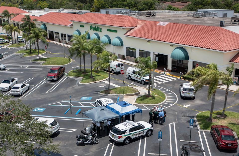 Police gather at a Publix shopping center where police say three people were shot and killed in Royal Palm Beach, Fla., on June 10.