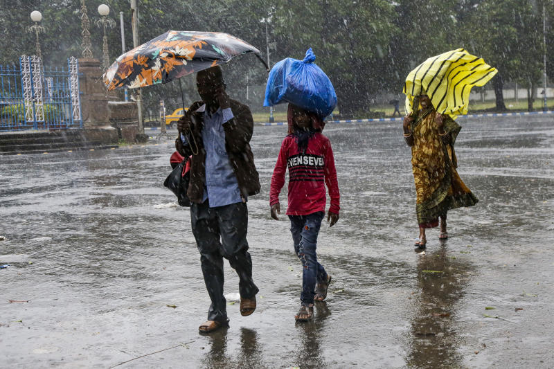 Indians walk in the rain in Kolkata, India, Saturday, Nov. 9, 2019. Authorities in nearby Bangladesh put more than 50,000 volunteers on standby and readied about 5000 shelters as a strong cyclone in the Bay of Bengal is expected to hit the low-lying nation's vast southwestern and southern coast on Saturday evening. (AP Photo/Bikas Das)