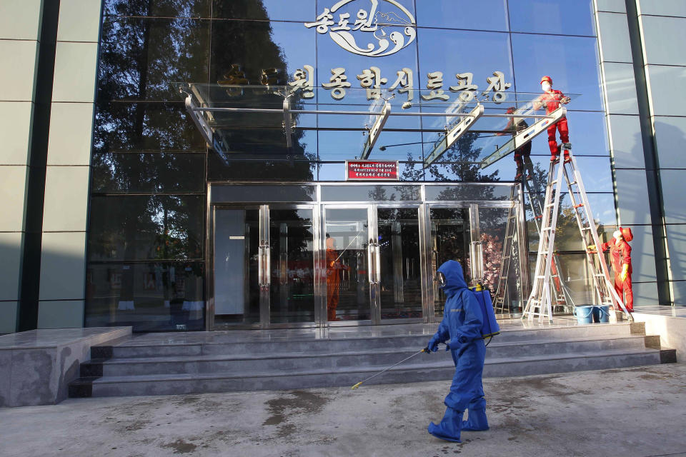 Hygienic and anti-epidemic officials disinfect the walkway outside the entrance to Songdowon General Foodstuff Factory in the city of Wonsan, Kangwon Province, North Korea DPRK, on Wednesday, Oct., 28, 2020. (AP Photo/Jon Chol Jin)