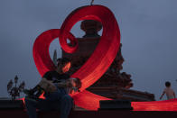 A woman holds a child near heart shaped art installation around a fountain in Beijing on Aug. 14, 2021. China will now allow couples to legally have a third child as it seeks to hold off a demographic crisis that could threaten its hopes of increased prosperity and global influence. (AP Photo/Ng Han Guan)