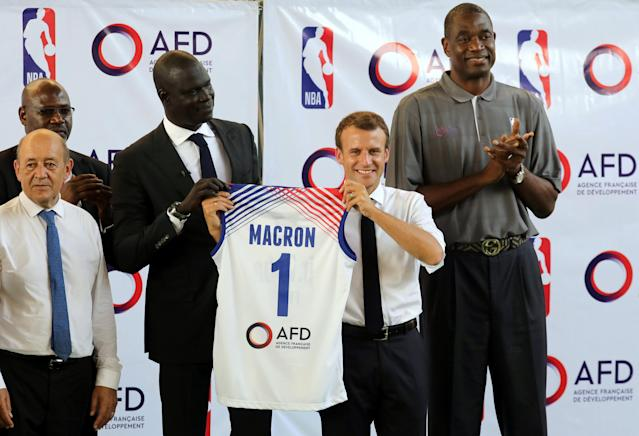 French President Emmanuel Macron recieves a basketball jersey from managing director of NBA Africa Amadou Gallo Fall (3rdR) flanked by French Foreign Affairs Minister Jean-Yves Le Drian (L) at the French Louis Pasteur high school in Lagos, Nigeria, July 4, 2018. Ludovic Marin/Pool via Reuters