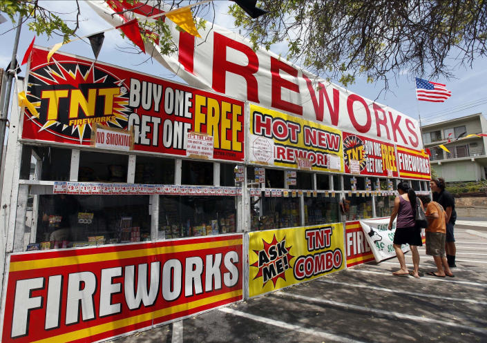 FILE - In this July 2, 2013, file photo, a family purchases fireworks at a TNT Fireworks stand in the City of Monterey Park, Calif. With fewer professional celebrations on July 4, 2020, due to the coronavirus pandemic, many Americans are bound to shoot off fireworks in backyards and at block parties. And they already are: Sales have been booming. (AP Photo/Nick Ut, File)