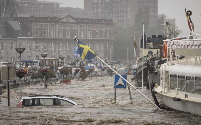A car floats in the Meuse River during heavy flooding in Liege, Belgium, Thursday, July 15, 2021. Heavy rainfall is causing flooding in several provinces in Belgium with rain expected to last until Friday. (AP Photo/Valentin Bianchi)