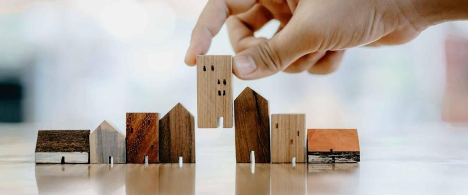 Hand choosing mini wood house models, representing different mortgage types