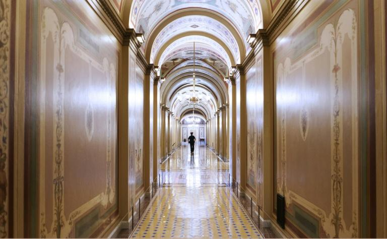 A lone Capitol police officer is seen in an empty corridor of the US Capitol in Washington, DC, where concerns are mounting about the coronavirus's effect on the older members of Congress