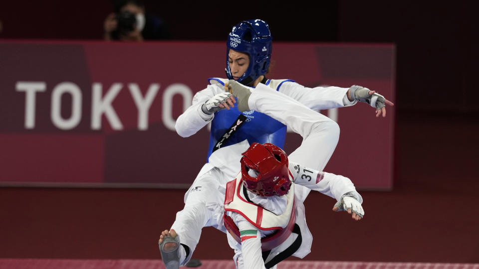 <p>Iran's Nahid Kiyani, front, attacks Kimia Alizadeh Zonoozi, of the Refugee Olympic Team, during the women's 57kg match at the 2020 Summer Olympics, Sunday, July 25, 2021, in Tokyo, Japan. (AP Photo/Themba Hadebe)</p>