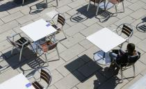 A customer waits to be served in an open terrace bar seen next to Palma de Mallorca's cathedral