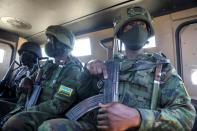 Soldiers from the Rwandan security forces sit inside an APC near the Afungi natural gas site