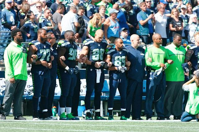 Members of the Seattle Seahawks are seen together during the playing of the national anthem before the start of an NFL game against the Miami Dolphins on September 11, 2016 in Seattle, Washington (AFP Photo/Otto Greule Jr)