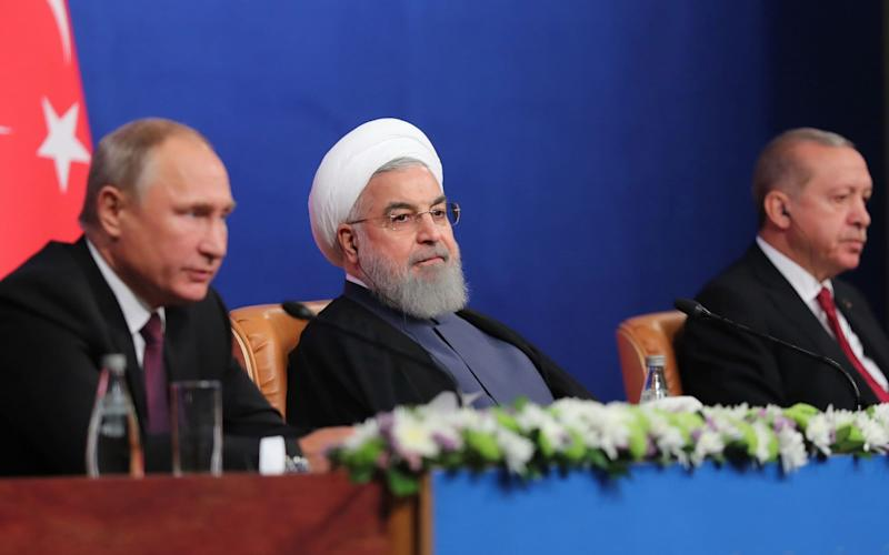 Vladimir Putin gives a press conference withIranian President Hassan Rouhani andTurkish President Recep Tayyip Erodgan last year - AFP