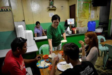 "Felicidad Magdayao, 59, owner of a fast-food restaurant serves customers in Manila, Philippines September 27, 2016. ""Our business has really suffered. People are afraid to go out. At dawn we only have few customers. At least, there are fewer drug addicts and drug pushers,"" she said. REUTERS/Ezra Acayan"