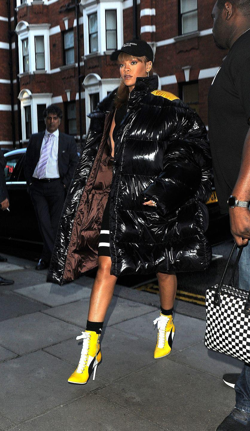 <p>Rihanna bundled up for a day of shopping at Harrods in London wearing a Raf Simons black puffer coat, yellow booties and her signature dad hat. </p>