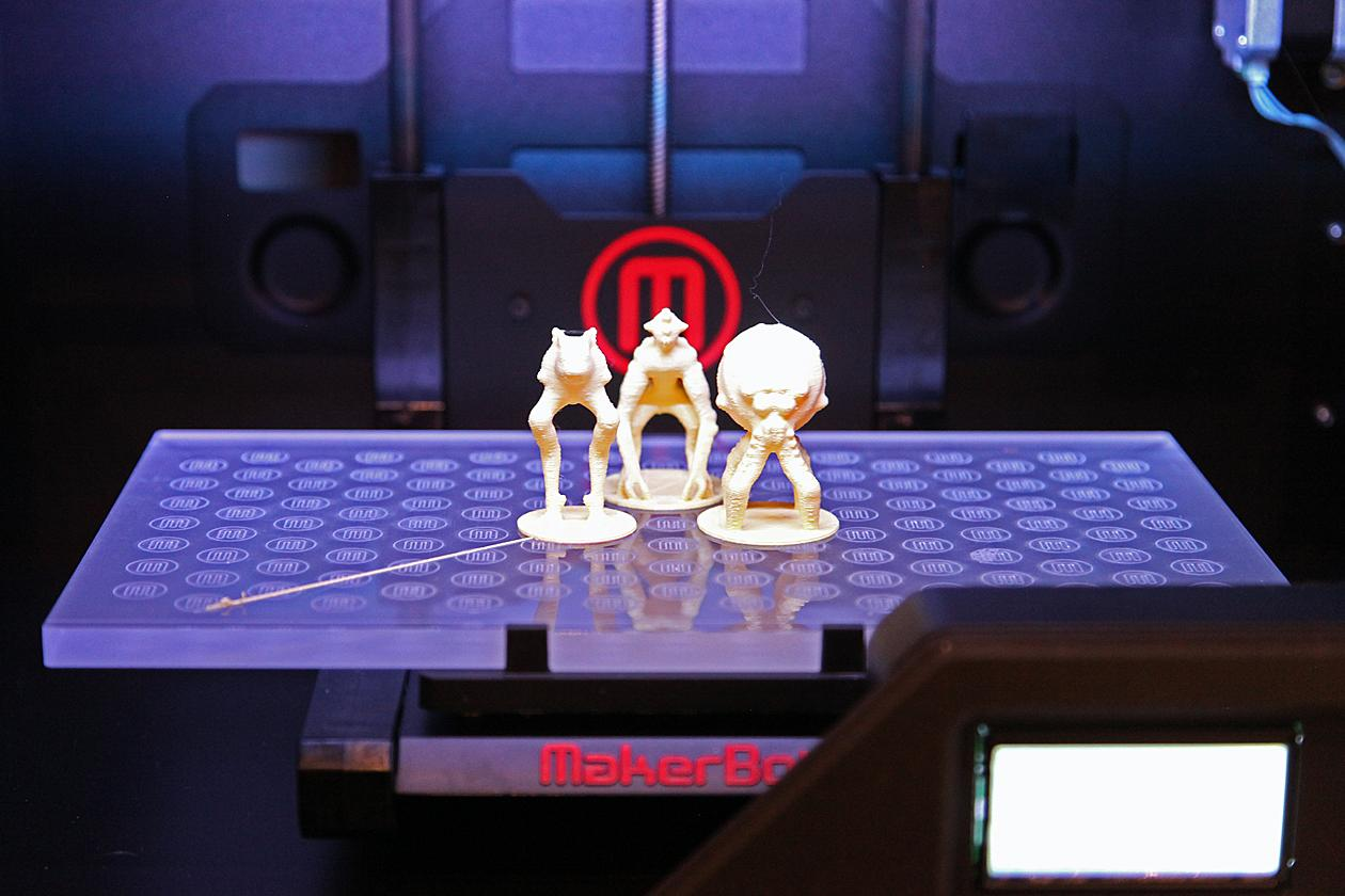 Printed models sitting inside a MakerBot Replicator 2 3D printer.