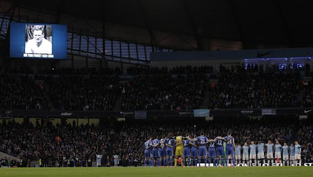 Manchester City, left and Chelsea soccer teams line up a hold a moment of silence for former England soccer player Sir Tom Finney, who died recently, prior to kick off for the English FA Cup fifth round soccer match at the Etihad Stadium, Manchester, England, Saturday, Feb. 15, 2014. (AP Photo/Jon Super)