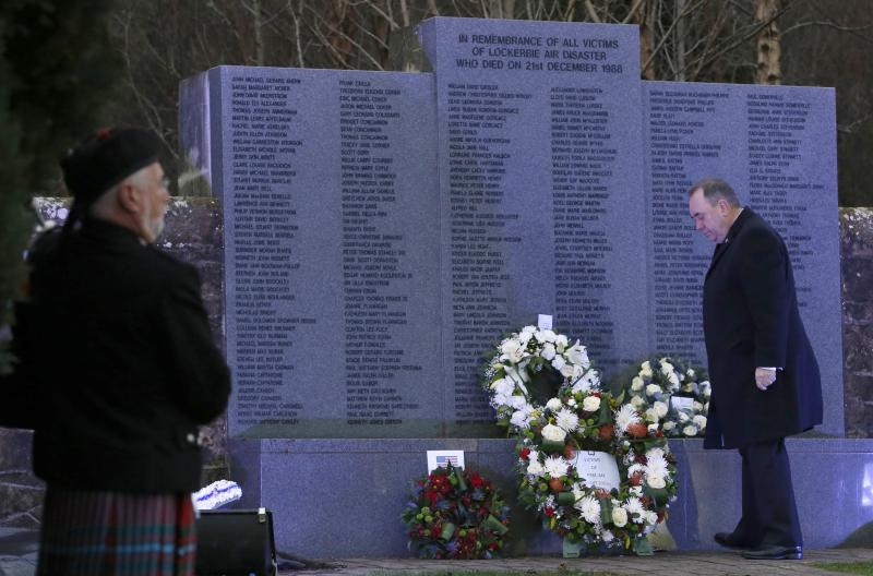 A piper watches as Scotland's First Minister Alex Salmond lays a wreath at a memorial event on the 25th anniversary of the bombing of Pan Am flight 103, in the Dryfesdale Cemetry, in Lockerbie, Scotland