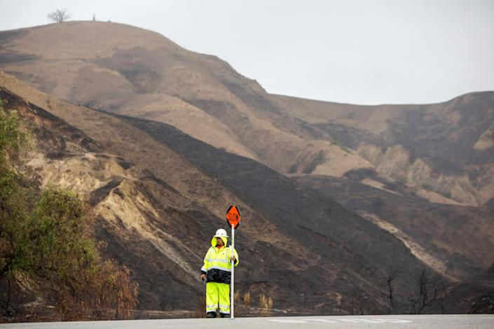 <p>Traffic is diverted on Foothill Road as workers place K-rail barricades along burn areas during a winter rain storm in Ventura, Calif., Jan. 9, 2018. (Photo: Monica Almeida/Reuters) </p>