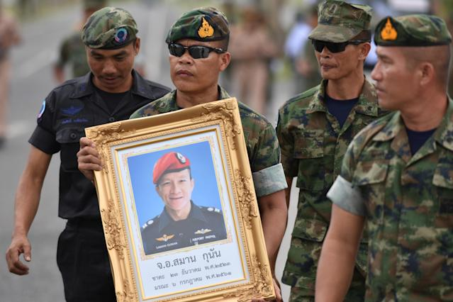 <p>An honor guard holds up a picture of Samarn Poonan, 38, a former member of Thailand's elite navy SEAL unit who died working to save 12 boys and their soccer coach trapped inside a flooded cave, in Rayong Province, Thailand, July 6, 2018. (Photo: Panumas Sanguanwong/Reuters) </p>