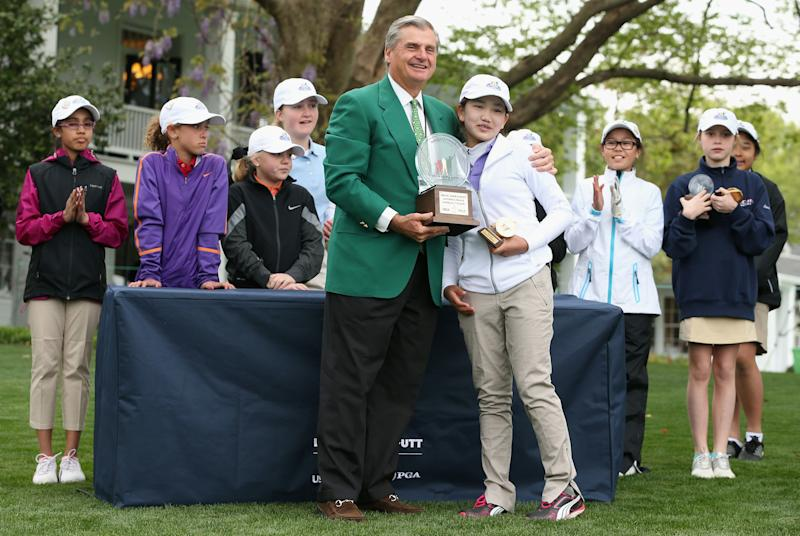 Li receives her trophy after winning the Girls 10-11 category at the National Finals of the inaugural Drive, Chip and Putt Championship in 2014.