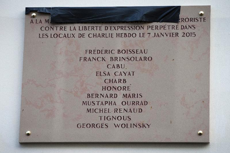 """A memorial plaque bearing the names of the victims of the Charlie Hebdo attack, with Georges Wolinski's name misspelled as """"Wolinsky"""""""