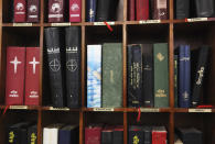 In this Sunday, Jan. 20, 2019 photo, Bibles and religious books in various languages are displayed on a bookshelf at St. Mary's Catholic Church in Dubai, United Arab Emirates. The diversity among its parishioners can be seen in its pews and heard the sermons of St. Mary's priests, who celebrate Mass and offer prayers in Arabic, English, French, Tagalog, Tamil, Urdu and other languages. Pope Francis' visit to the United Arab Emirates starting Sunday Feb. 3, marks the first ever papal visit to the Arabian Peninsula, the birthplace of Islam. (AP Photo/Jon Gambrell)