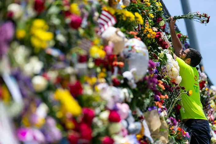 Leo Soto places flowers at the Surfside Wall of Hope & Memorial as rescue teams continue their recovery mission at the collapsed Champlain Towers South Condo building in Surfside, Florida on Friday, July 9, 2021. The memorial has grown since it was first created shortly after the collapse.