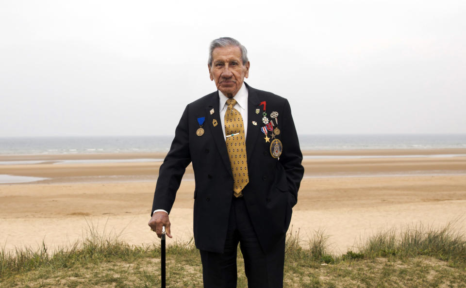 In this May 1, 2019, photo, World War II and D-Day veteran Charles Norman Shay, from Indian Island, Maine, poses on a dune at Omaha Beach in Saint-Laurent-sur-Mer, Normandy, France. Shay was a medic who on June 6, 1944, landed on Omaha Beach, where he helped drag wounded soldiers out of the rising tide, saving them from drowning. For his courage, he was awarded the Silver Star. (AP Photo/Virginia Mayo)