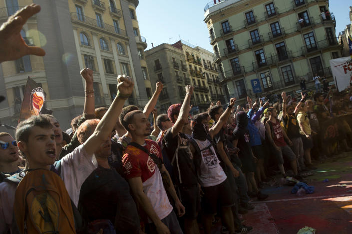 Pro independence demonstrators react as they are stop by Catalan police officers on their way to meet demonstrations by member and supporters of National Police and Guardia Civil, as coloured powder is seen in the air after being thrown by protesters, in Barcelona on Saturday, Sept. 29, 2018. (AP Photo/Emilio Morenatti)