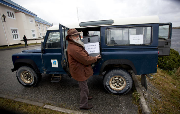 Voting observer Phil Middleton carries a ballot box inside his car to take it to a polling station in Port Stanley, Falkland Islands, Sunday, March 10, 2013. The local Falkland Islands Government has mobilized a major effort to get as many of its 1,650 registered voters as possible to cast their secret ballots Sunday and Monday, preparing to send off-road vehicles, boats and seaplanes to remote sheep farms across the lightly populated islands. (AP Photo/Paul Byrne)