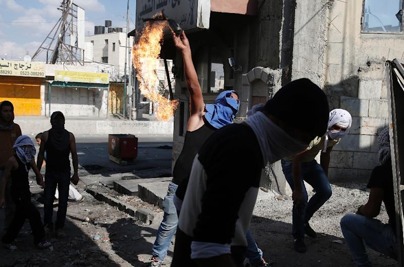 A masked Palestinian youth throws a petrol bomb towards Israeli security forces during clashes at the Qalandia checkpoint between Jerusalem and Ramallah, in the Israeli-occupied West Bank, on October 6, 2015 (AFP Photo/Abbas Momani)