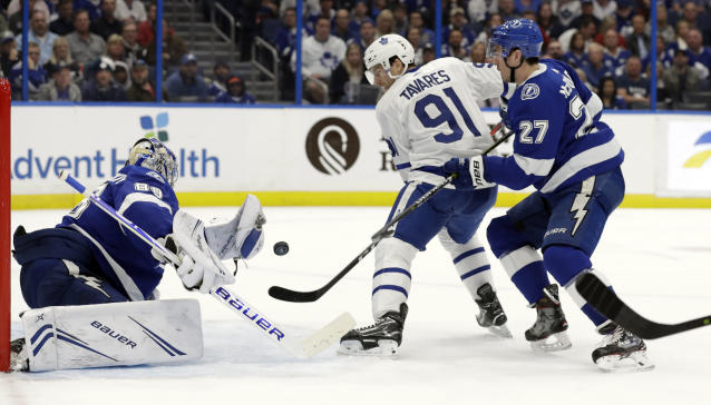 Tampa Bay Lightning goaltender Andrei Vasilevskiy (88) reaches for a shot by Toronto Maple Leafs center John Tavares (91) as defenseman Ryan McDonagh (27) closes in during the first period of an NHL hockey game, Thursday, Jan. 17, 2019, in Tampa, Fla. (AP Photo/Chris O'Meara)