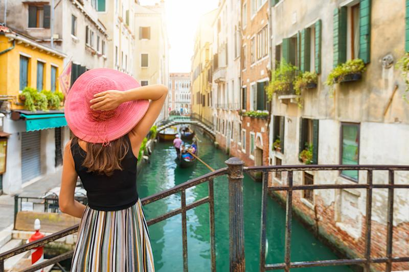 The back of a woman standing on a bridge over a canal in Venice