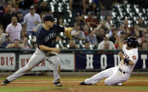 Houston Astros' Jose Altuve (27) slides safely under the ball and past Seattle Mariners third baseman Kyle Seager (15) on a Fernando Martinez single in the third inning of a baseball game Tuesday, April 23, 2013, in Houston. (AP Photo/Pat Sullivan)