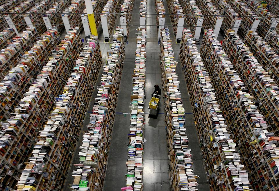 FILE PHOTO: A worker gathers items for delivery from the warehouse floor at Amazon's distribution center in Phoenix, Arizona November 22, 2013.  REUTERS/Ralph D. Freso/File Photo