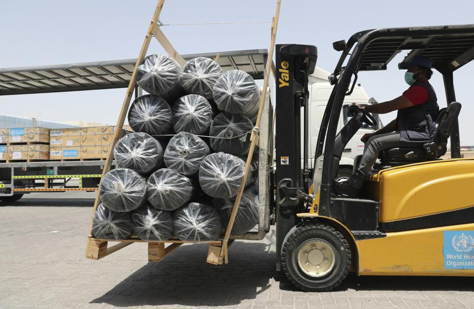 A forklift driver loads material for temporary shelters to be sent to India, at the UNHCR warehouses, part of the International Humanitarian City, in Dubai, United Arab Emirates, Sunday, May 9, 2021. Dubai's long-haul carrier Emirates will begin shipping aid from the World Health Organization and other groups into India for free to help fight a crushing outbreak of the coronavirus, the airline said Sunday. (AP Photo/Kamran Jebreili)