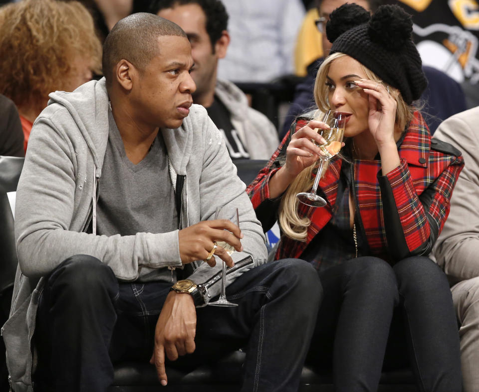 Jay-Z and Beyonce pop some champagne on the sidelines of a 76ers-Nets showdown. (AP)