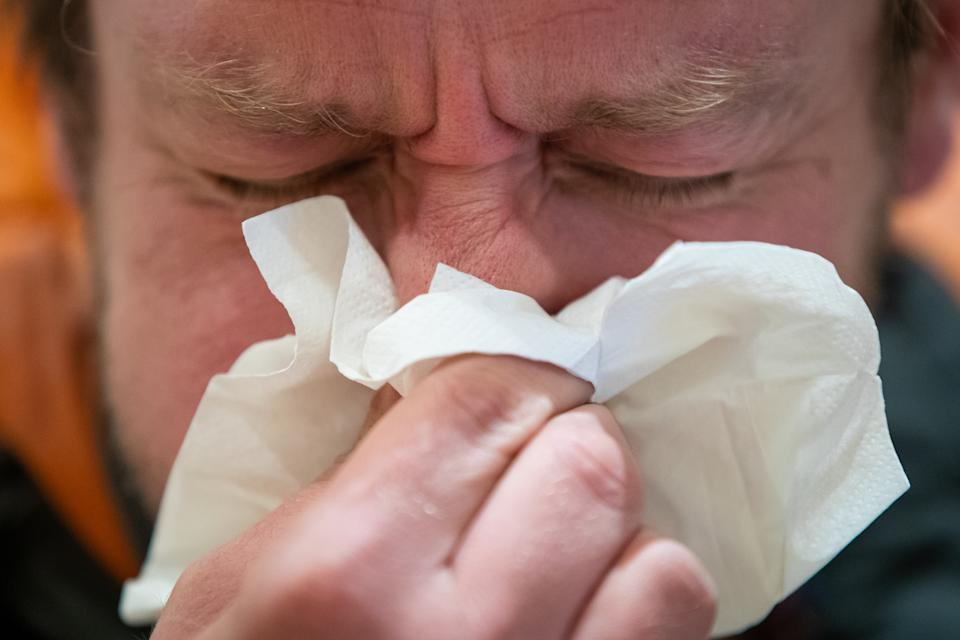 """A picture posed by a model of a man blowing his nose into a tissue in London. England's deputy chief medical officer Dr Jenny Harries has said that """"many thousands of people"""" would contract coronavirus as the disease continued to spread in the UK. PA Photo. Picture date: Wednesday March 11, 2020. See PA story HEALTH Coronavirus. Photo credit should read: Aaron Chown/PA Wire (Photo by Aaron Chown/PA Images via Getty Images)"""