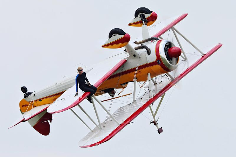 A wing walker performs at the Vectren Air Show just before crashing, Saturday, June 22, 2013, in Dayton, Ohio. The crash killed the pilot and the stunt walker instantly, authorities said. (AP Photo/Thanh V Tran)
