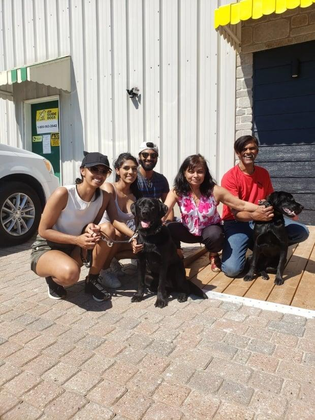 Guide dogs are trained by host families, and there's no guarantee of success even after two years. Here the Hettiarachchi family in Scarborough, Ontario, poses with Jess before the dog was assigned to Yukon.