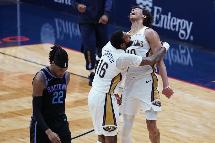 New Orleans Pelicans center Jaxson Hayes reacts with forward James Johnson (16) in front of Sacramento Kings center Richaun Holmes (22) after his slam dunk in the first half of an NBA basketball game in New Orleans, Monday, April 12, 2021. (AP Photo/Gerald Herbert)