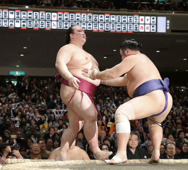In this Tuesday, Jan. 15, 2019, photo, grand champion Kisenosato, left, is pushed out of the ring by Tochiozan at the New Year Grand Sumo Tournament in Tokyo. Kisenosato, the only Japanese wrestler at sumo's highest rank, has decided to retire after three straight losses at the tournament. (Kyodo News via AP)