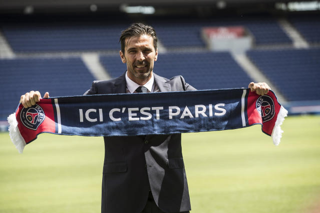 "PSG's new signing goalkeeper Gianluigi Buffon displays a scarf reading ""here is Paris"" during his official presentation at the Parc des Princes stadium in Paris, France, Monday, July 9, 2018. Free agent Gianluigi Buffon signed for Paris Saint-Germain last Friday. The veteran goalkeeper penned a one-year deal at the French champion with the option for an additional season. (AP Photo/Jean-Francois Badias)"