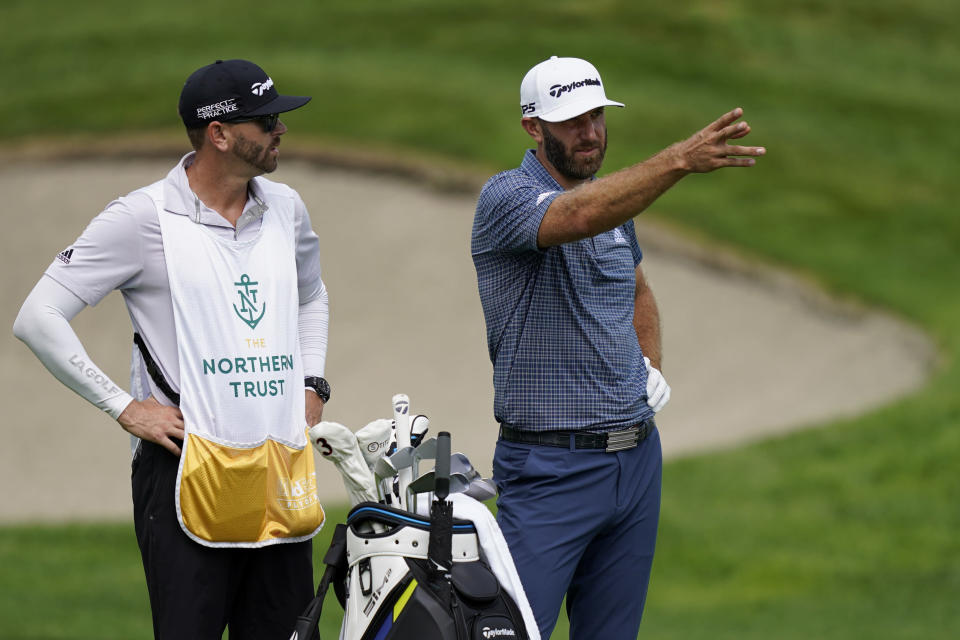 Dustin Johnson, right, speaks with his caddie on the eighth fairway in the first round of play at the Northern Trust golf tournament, Thursday, Aug. 19, 2021, at Liberty National Golf Course in Jersey City, N.J. (AP Photo/John Minchillo)