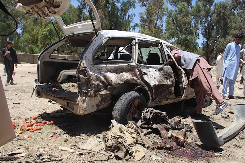 Afghan residents gather at the scene of a suicide car bomb that targeted a CIA-funded pro-government militia force at a public bus station in Khost province on May 27, 2017 (AFP Photo/Farid Zahir)