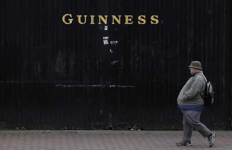A man passes the Guinness beer factory in the city centre of Dublin