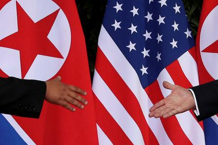 FILE PHOTO - U.S. President Trump and North Korea's Kim meet at the start of their summit in Singapore