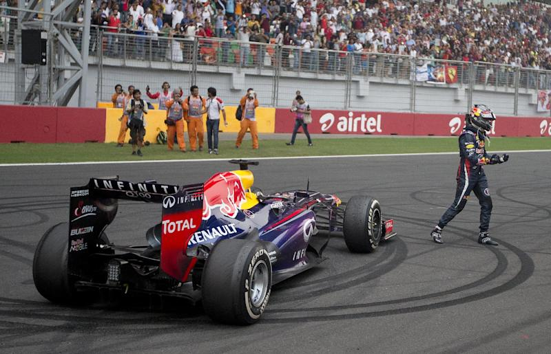 Red Bull driver Sebastian Vettel of Germany celebrates on the track after winning the Indian Formula One Grand Prix and his 4th straight F1 world championship at the Buddh International Circuit in Noida, India, Sunday, Oct. 27, 2013. (AP Photo/Mark Baker)