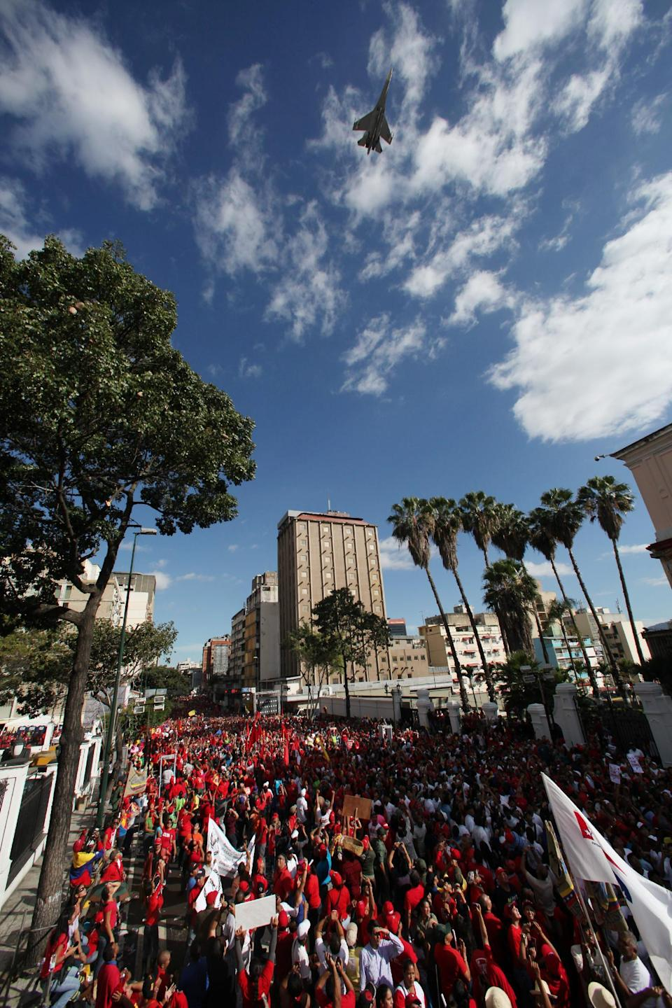 FILE - In this Jan. 10, 2013 file photo, a military plane flies over supporters of Venezuela's President Hugo Chavez gathered outside Miraflores presidential palace for Chavez's symbolic inauguration ceremony in Caracas, Venezuela. Since taking office in 1999, Chavez has tried to transform the military into defenders of his socialist-inspired policies, especially since a 2002 coup led by rebellious soldiers. Briefly dislodged from power, Chavez returned to the presidential palace only after loyalists within the military stepped in to put down the coup. (AP Photo/Fernando Llano, File)