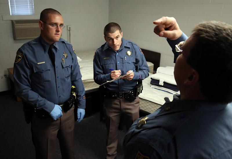 Simulating a roadside investigation of a potentially intoxicated driver, Colorado State Trooper Corporal R.P. Meyers, right, pretends to be high as he trains troopers Josh Pritchett, left, and Louis Anderson in a several week long Drug Recognition Expert class, at the Colorado State Patrol Training Academy, in Golden, Colo., Thursday March 6, 2014. The ongoing training is happening as Colorado struggles to keep accurate statewide records on marijuana-impaired drivers, with state police chiefs saying they need more money to train officers in recognizing stoned drivers. (AP Photo/Brennan Linsley)