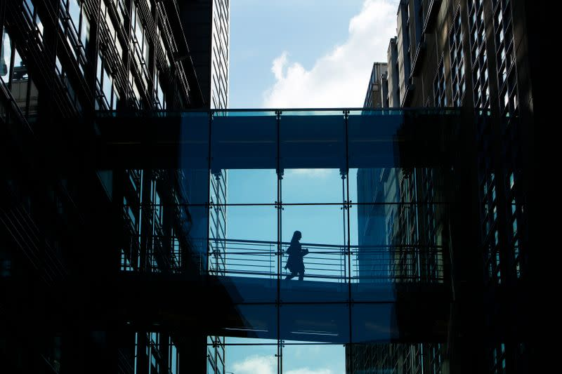A woman crosses a walkway between Goldman Sachs offices in central London