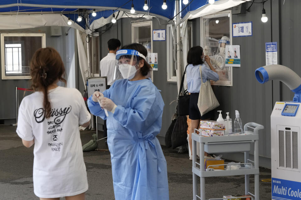 Medical workers takes nasal samples from residents for coronavirus tests at a makeshift testing site in Seoul, South Korea, Tuesday, July 20, 2021. (AP Photo/Ahn Young-joon)